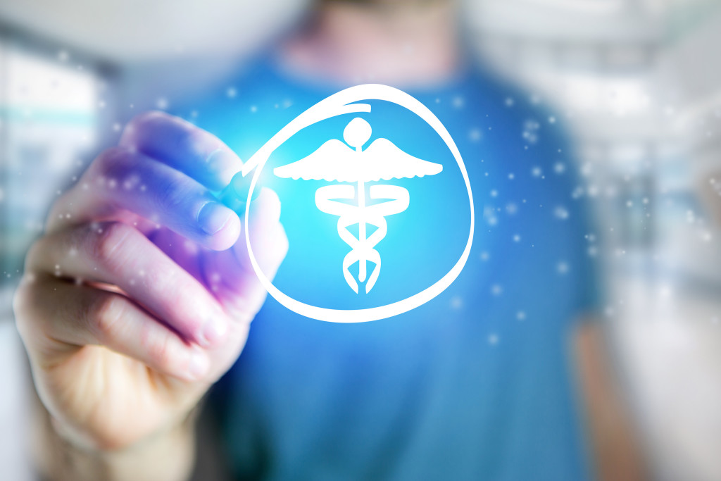Man drawing a medical icon on a futuristic interface - Technology concept