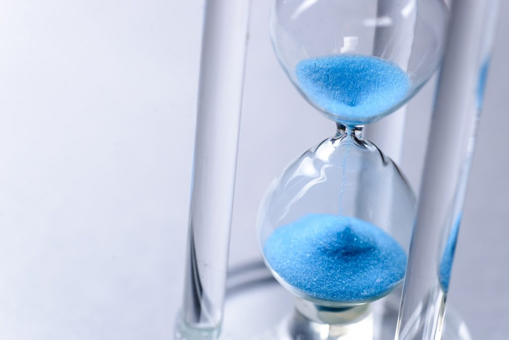 Close-up studio shot of hourglass with blue sand